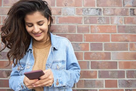 Beautiful young woman sending a text message Stock Photo