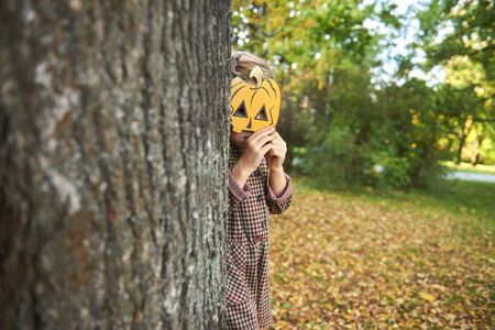Little girl holding halloween pumpkin in front of his face