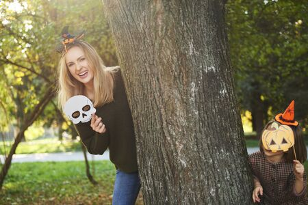 Mother and her daughter in halloween masks in autumn forest