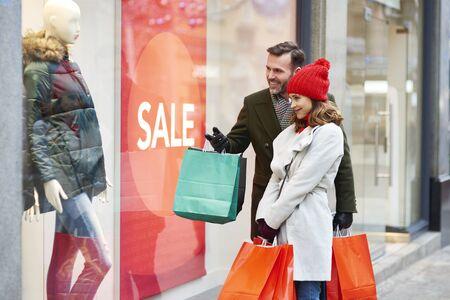 Happy couple looking at big shop display