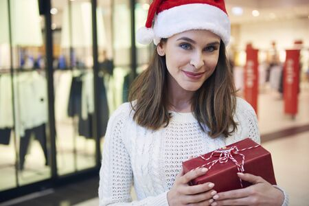 Beautiful woman with Christmas present in the shopping mall