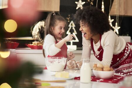 Mother and daughter enjoying in the kitchen at Christmas 版權商用圖片