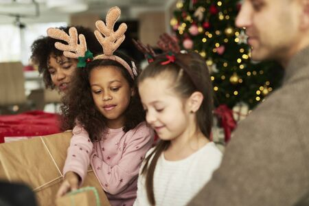 Children opening Christmas presents with parents