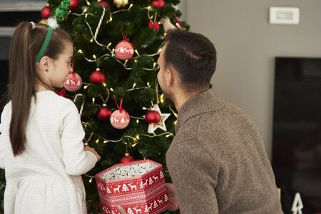 Rear view of girl and dad decorating the Christmas tree