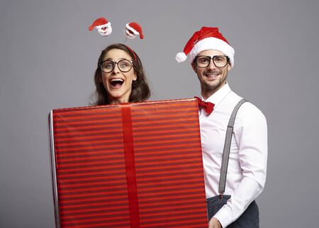 Playful couple with big Christmas gift
