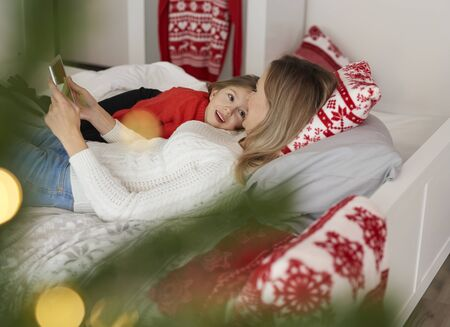 Woman and her daughter using mobile phone at Christmas 스톡 콘텐츠