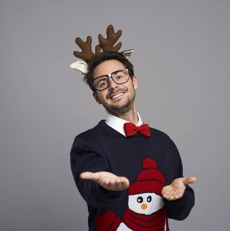 Portrait of man in Christmas clothes with palm of hand