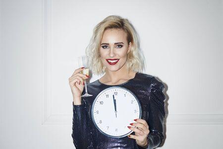 Portrait of beautiful woman holding champagne and clock Archivio Fotografico