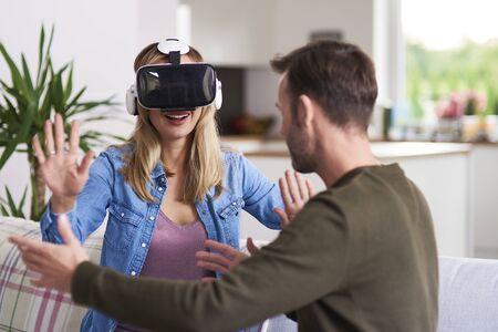 Modern woman using virtual reality simulator in living room Archivio Fotografico