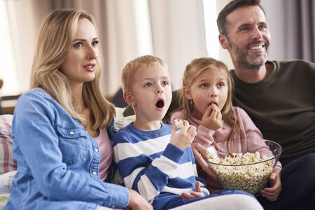 Family with two children watching TV in living room