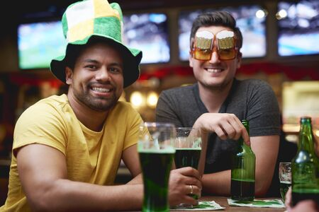 Men with leprechauns hat and beer celebrating Saint Patricks Day