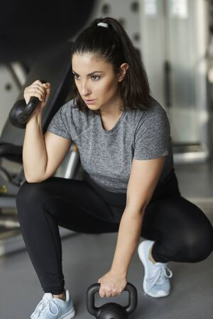 Young woman with kettlebell exercising at gym