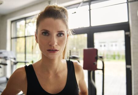 Waist up of serious woman at gym