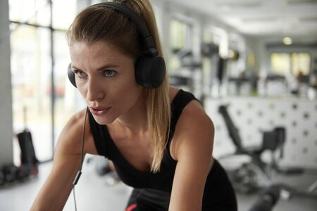 Sporty woman working out with exercise bike