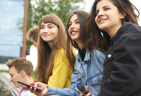 Three young women meeting in the city Stockfoto