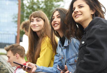 Tres mujeres jóvenes reunidas en la ciudad. Foto de archivo