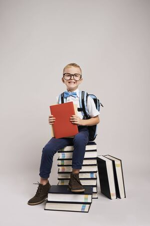 Portrait of smiling child among a stack of books
