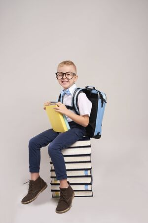 Happy child with backpack and stack of books Reklamní fotografie