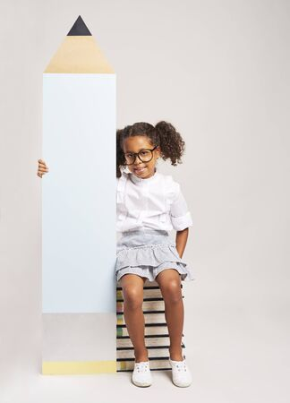 African girl sitting on books and holding big pencil