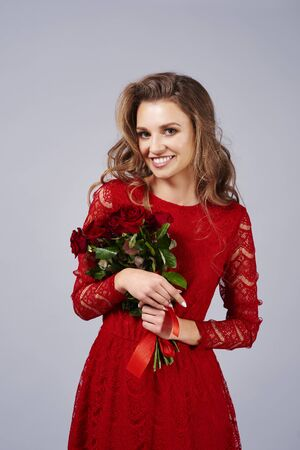 Portrait of beautiful woman holding a bunch of red roses 写真素材