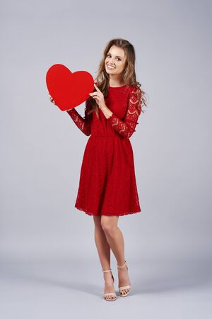 Beautiful  woman holding a big, red heart 写真素材