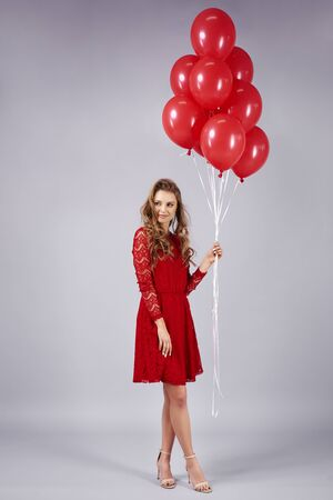 Beautiful young woman with bunch of balloons