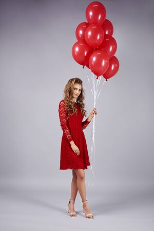 Portrait of beautiful woman holding a bunch of balloons