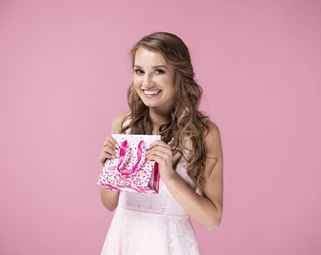 Smiling woman with gift bag on the pink background