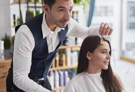 Jeune femme et coiffeur choisissant de couleur pour teindre les cheveux