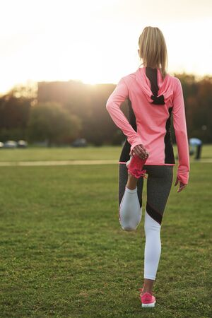 Rear view of woman warming up before jogging