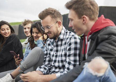Friends checking news by mobile phone Reklamní fotografie
