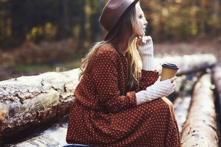 Side view of beautiful woman drinking coffee in autumn forest Reklamní fotografie