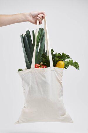 Human hand holding bag of fresh vegetable