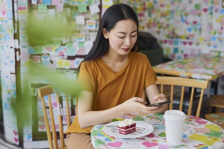 Young Vietnamese woman looking at mobile phone in a cafe