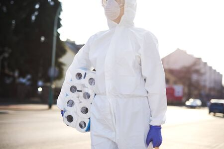 Unrecognizable person in protective suit walking with some shopping