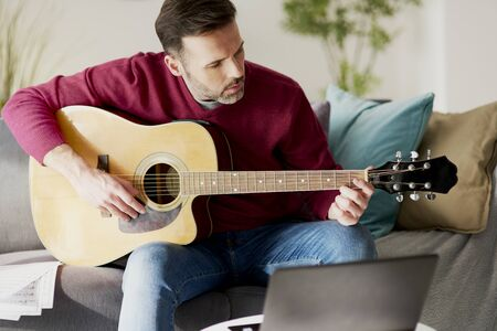 Mid age man playing an acoustic guitar