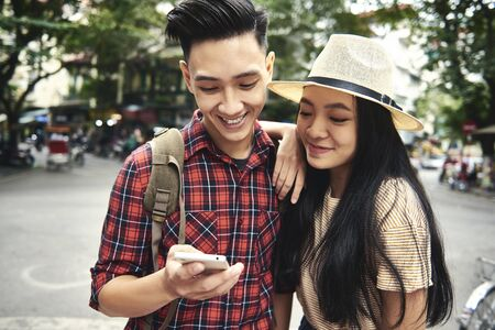 Young couple using mobile phone while traveling Foto de archivo