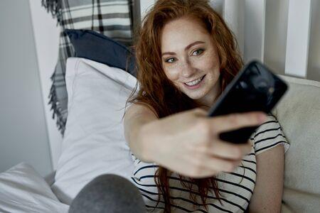 Woman taking selfie in the bedroom Standard-Bild