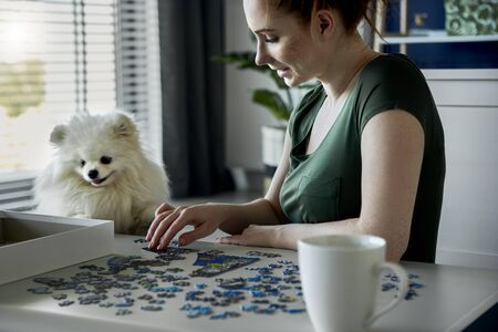 Young woman doing jigsaw puzzles