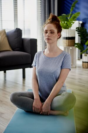 Vertical image of woman meditating at home