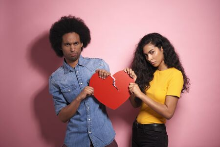 Sad African couple breaking the red heart in studio shot. Stock Photo