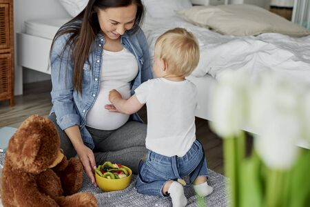 Little brother feeding with fruits his future sibling