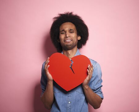 Portrait of distraught African man with a broken red heart.