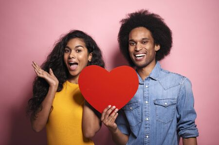 Happiness  African couple holding a red heart in studio shot.