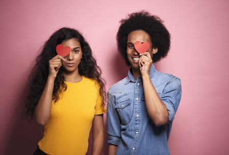 Young African couple covering eyes by hearts in studio shot. Stock Photo