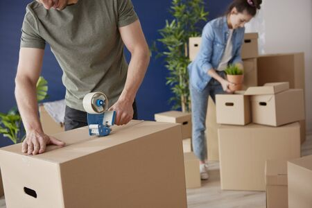 Couple packing cardboard boxes while moving house