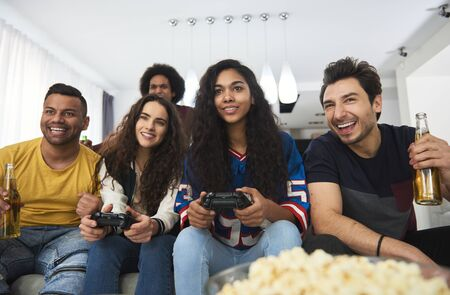 Group of friends playing on the console at home