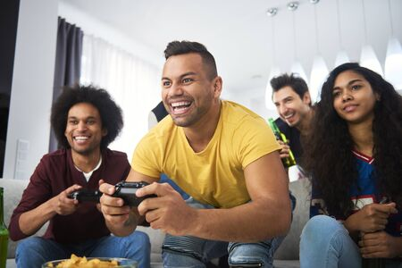 Excited boys playing console with friends