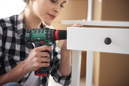Independent woman repairing furnitures with electronic drill Stock Photo