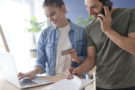 Happy couple doing shopping online for new house Stock Photo